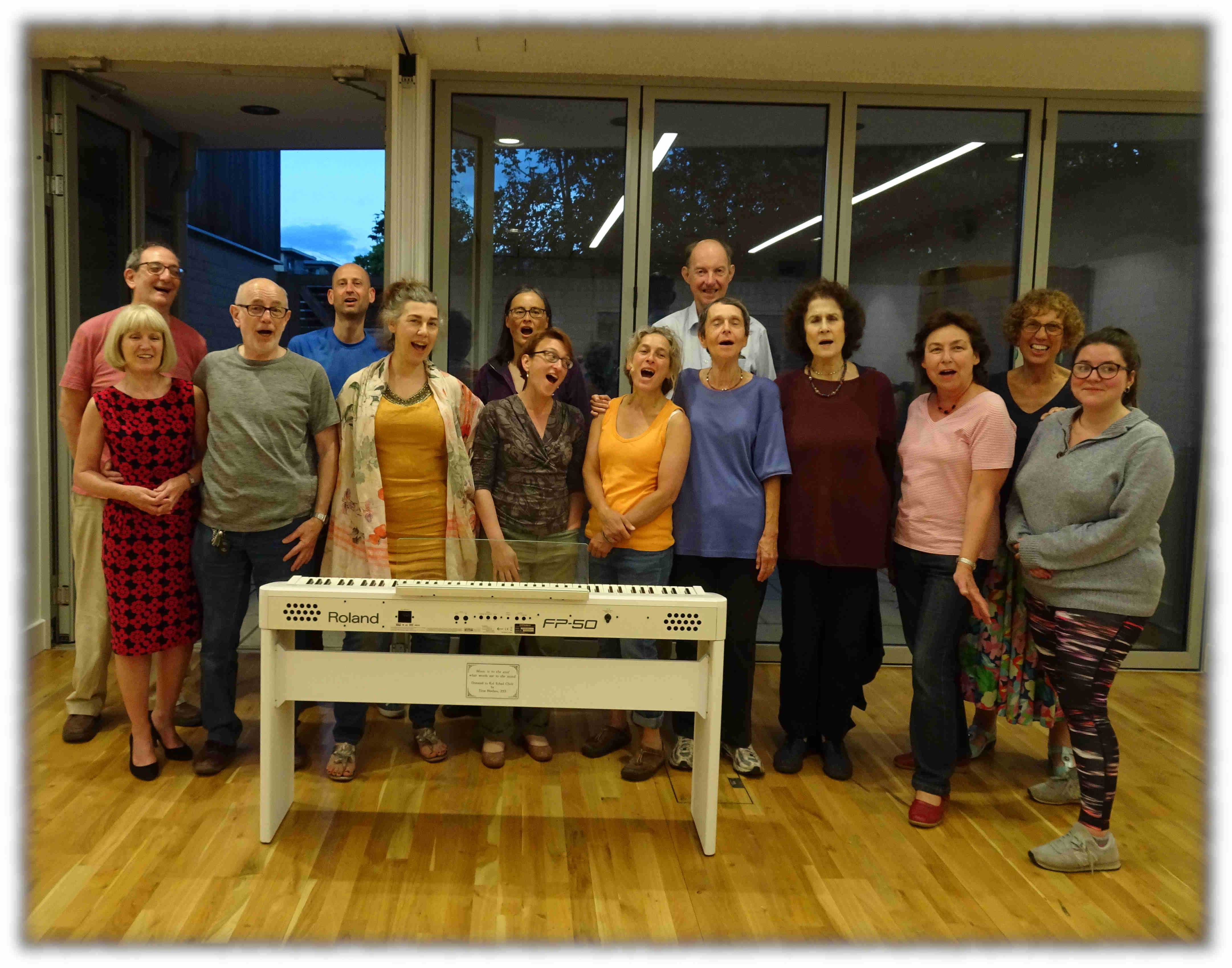 Kol Echad Choir group photo. Members standing next to a piano and singing joyfully.